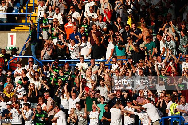 Swansea fans cheer during the Barclays Premier League match between Chelsea and Swansea City at Stamford Bridge on August 8 2015 in London England