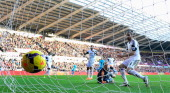 Swansea keeper Gerhard Tremmel turns to see Swansea defender Chico Flores turn a Kyle Walker cross into his own net for the second Spurs goal during...