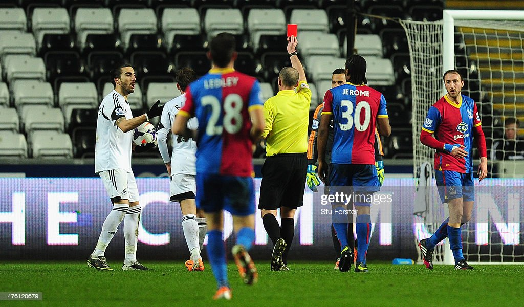 Swansea player Chico Flores (l) is sent off by referee Mike Dean during the Barclays Premier League match between Swansea City and Crystal Palace at Liberty Stadium on March 2, 2014 in Swansea, Wales.
