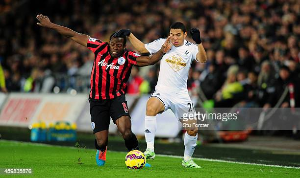Swansea player Jefferson Montero is challenged by QPR player Nedum Onuoha during the Barclays Premier League match between Swansea City and Queens...