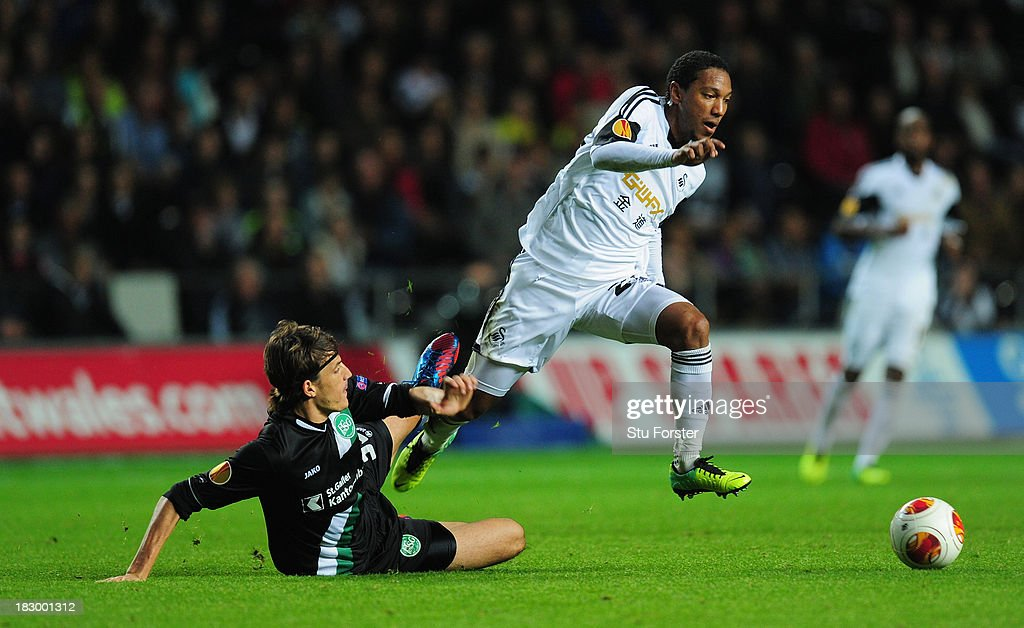 Swansea player Jonathan De Guzman (r) skips the challenge of St Gallen defender Daniele Russo during the UEFA Europa League match between Swansea City and FC St Gallen at Liberty Stadium on October 3, 2013 in Swansea, Wales.