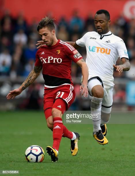 Swansea player Jordan Ayew challenges Kiko Femenia of Watford during the Premier League match between Swansea City and Watford at Liberty Stadium on...