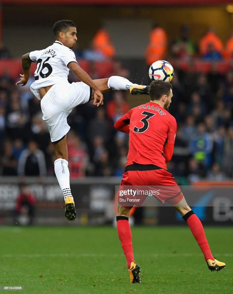 Swansea player Kyle Naughton (l) challenges Scott Malone of Town to the ball during the Premier League match between Swansea City and Huddersfield Town at Liberty Stadium on October 14, 2017 in Swansea, Wales.