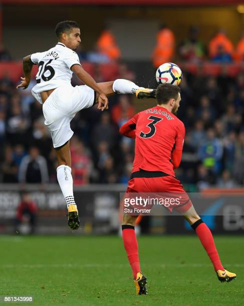 Swansea player Kyle Naughton challenges Scott Malone of Town to the ball during the Premier League match between Swansea City and Huddersfield Town...