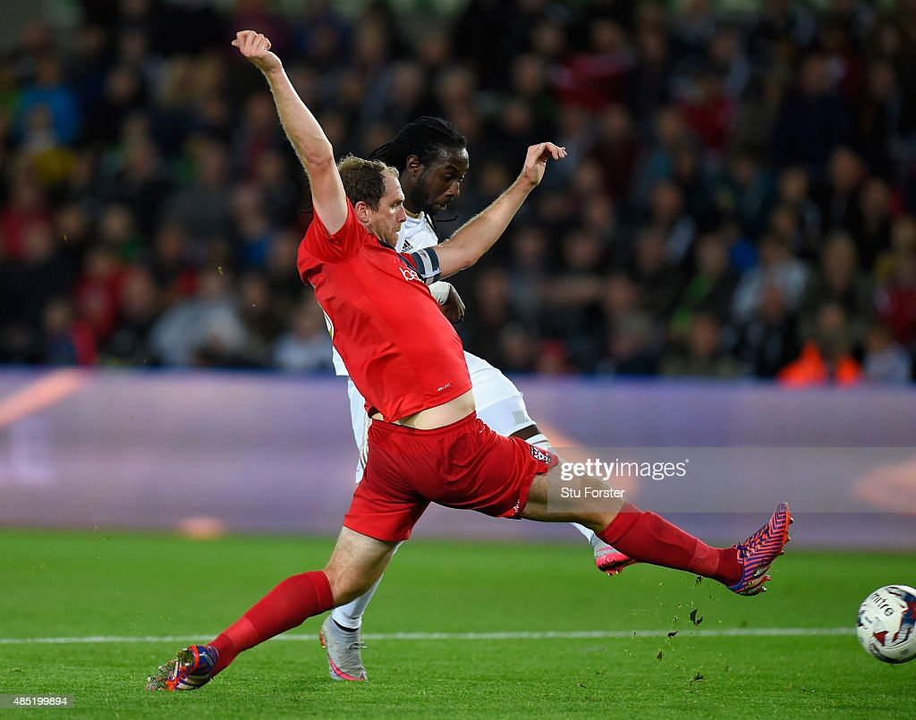 Swansea player Marvin Emnes (r) scores the third goal despite the attentions of Keith Lowe of York City during the Capital One Cup Second Round match between Swansea City and York City at Liberty Stadium on August 25, 2015 in Swansea, Wales.