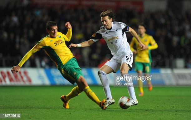 Swansea player Michu beats Artem Fidler to the ball during the UEFA Europa League Group A match between Swansea City and FC Kuban Krasnodar at...