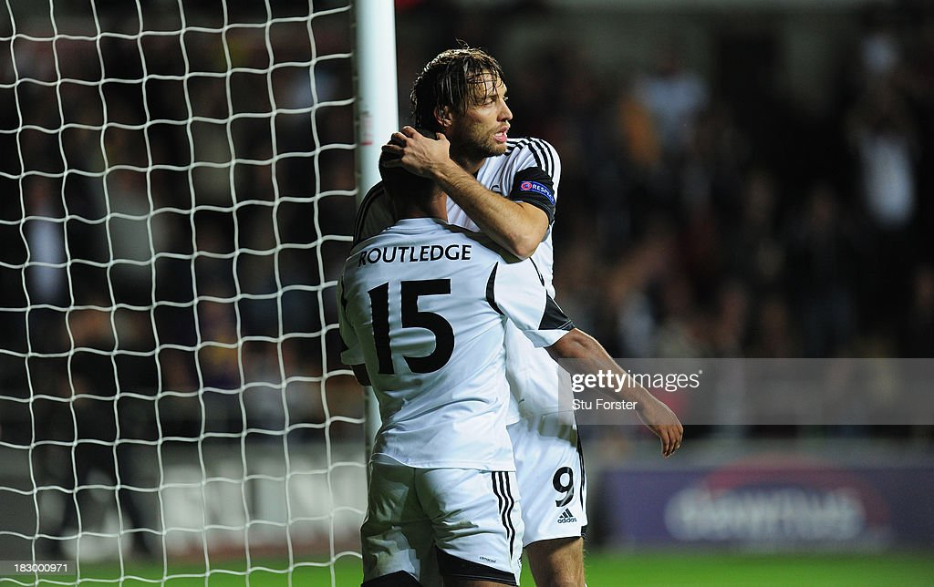 Swansea player Michu (r) celebrates with goalscorer Wayne Routledge after the first Swansea goal during the UEFA Europa League match between Swansea City and FC St Gallen at Liberty Stadium on October 3, 2013 in Swansea, Wales.
