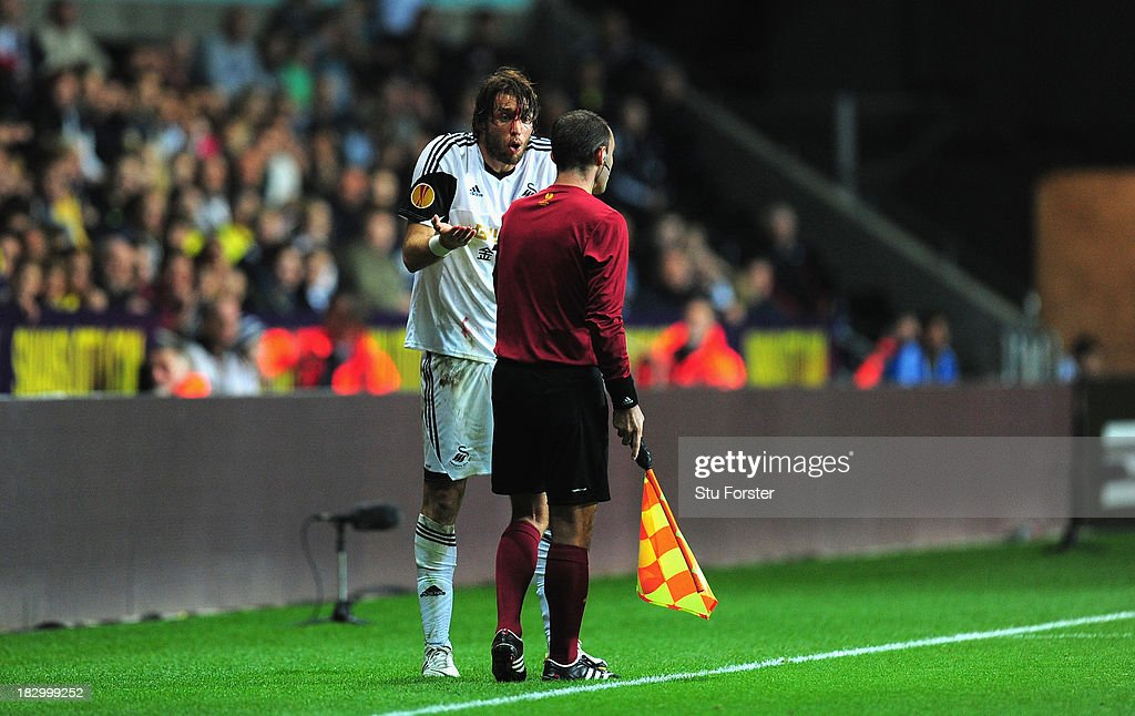 Swansea player Michu shows his bloodied head wound to the linesman during the UEFA Europa League match between Swansea City and FC St Gallen at Liberty Stadium on October 3, 2013 in Swansea, Wales.