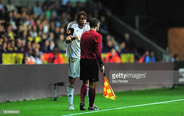 Swansea player Michu shows his bloodied head wound to the linesman during the UEFA Europa League match between Swansea City and FC St Gallen at...