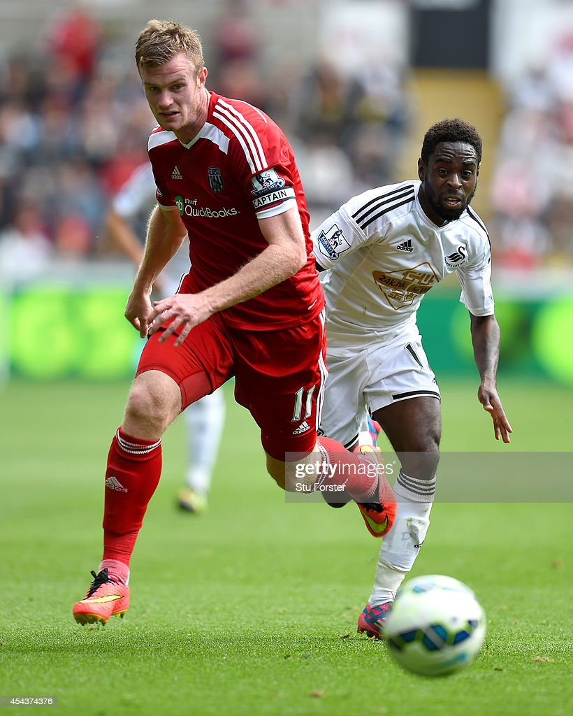 Swansea player Nathan Dyer challenges Chris Brunt of West Brom during the Barclays Premier League match between Swansea City and West Bromwich Albion at Liberty Stadium on August 30, 2014 in Swansea, Wales.