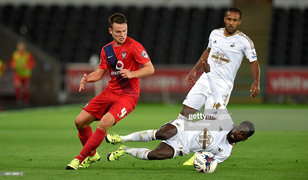 Swansea player Nathan Dyer (floor) challenges James Berrett of York during the Capital One Cup Second Round match between Swansea City and York City at Liberty Stadium on August 25, 2015 in Swansea, Wales.