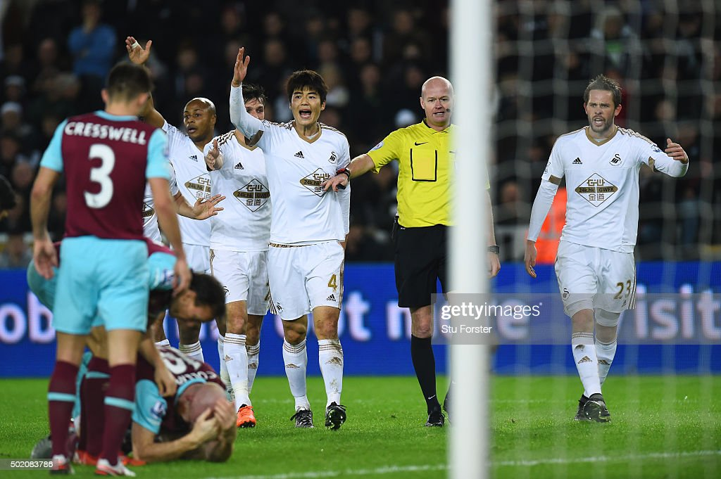 Swansea players appeal to referee <a gi-track='captionPersonalityLinkClicked' href=/galleries/search?phrase=Lee+Mason&family=editorial&specificpeople=221143 ng-click='$event.stopPropagation()'>Lee Mason</a> after <a gi-track='captionPersonalityLinkClicked' href=/galleries/search?phrase=James+Collins+-+Joueur+de+football+gallois&family=editorial&specificpeople=15167252 ng-click='$event.stopPropagation()'>James Collins</a> (ground) of West Ham appeared to handle the shot from Ki Sung-Yeung of Swansea City during the Barclays Premier League match between Swansea City and West Ham United at the Liberty Stadium on December 20, 2015 in Swansea, Wales.