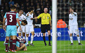 Swansea players appeal to referee Lee Mason after James Collins of West Ham appeared to handle the shot from Ki SungYeung of Swansea City during the...
