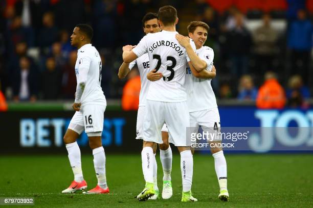 Swansea players celebrate on the pitch after the English Premier League football match between Swansea City and Everton at The Liberty Stadium in...