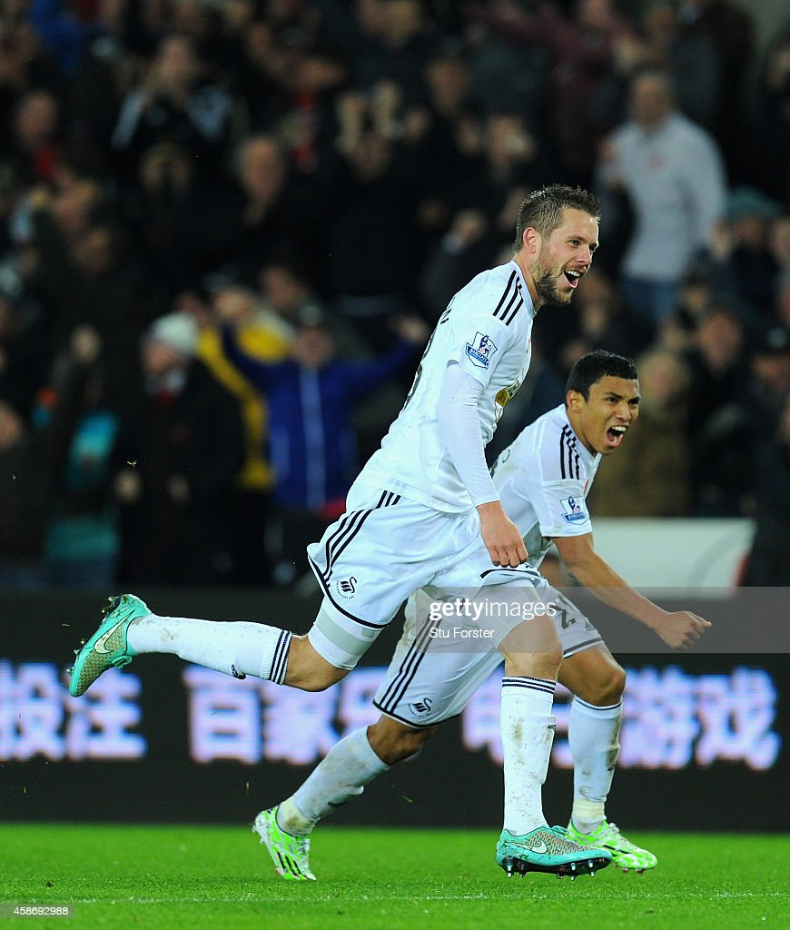 Swansea players Gylfi Sigurdsson (l) and Jefferson Montero celebrate the first Swansea goal during the Barclays Premier League match between Swansea City and Arsenal at Liberty Stadium on November 9, 2014 in Swansea, Wales.