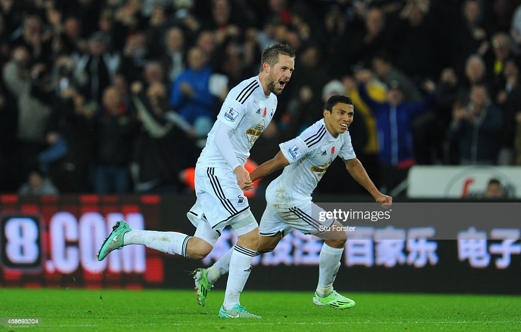 Swansea players <a gi-track='captionPersonalityLinkClicked' href=/galleries/search?phrase=Gylfi+Sigurdsson&family=editorial&specificpeople=6401581 ng-click='$event.stopPropagation()'>Gylfi Sigurdsson</a> (l) and <a gi-track='captionPersonalityLinkClicked' href=/galleries/search?phrase=Jefferson+Montero&family=editorial&specificpeople=4406087 ng-click='$event.stopPropagation()'>Jefferson Montero</a> celebrate the first Swansea goal during the Barclays Premier League match between Swansea City and Arsenal at Liberty Stadium on November 9, 2014 in Swansea, Wales.