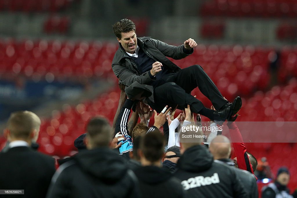 Swansea players lift up Manager of Swansea City Michael Laudrup after their 5-0 victory in the Capital One Cup Final match between Bradford City and Swansea City at Wembley Stadium on February 24, 2013 in London, England.
