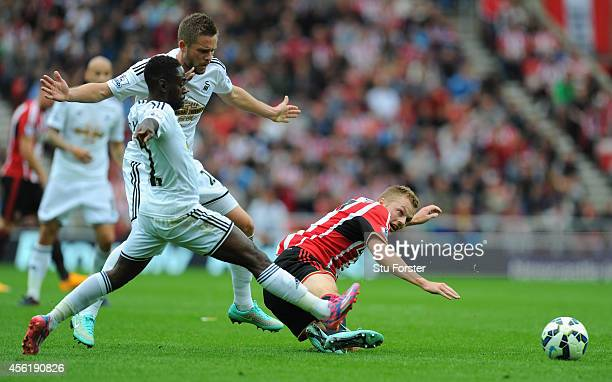 Swansea players Nathan Dyer and Gylfi Sigurdsson challenge Sebastian Larsson of Sunderland during the Barclays Premier League match between...