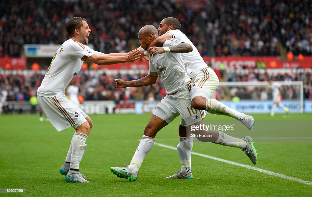 Swansea striker Andre Ayew (c) celebrates with Ashley Williams 9r0 and Gylfi Sigurdsson (l) after scoring the first swansea goal during the Barclays Premier League match between Swansea City and Manchester United on August 30, 2015 in Swansea, United Kingdom.
