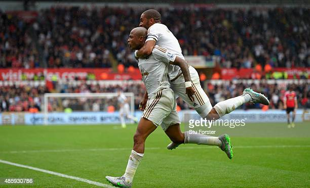 Swansea striker Andre Ayew celebrates with Ashley Williams after scoring the first swansea goal during the Barclays Premier League match between...