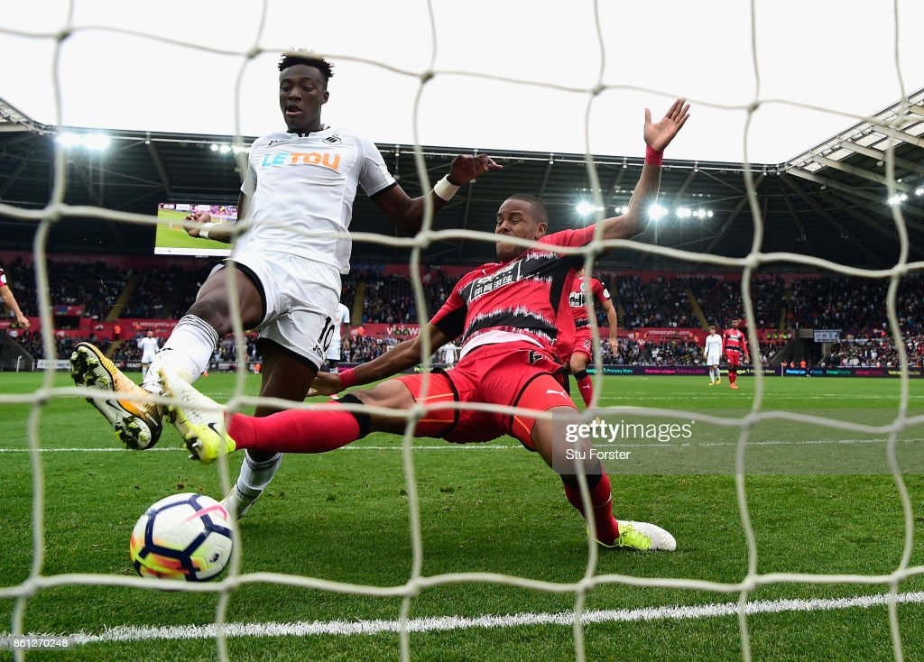 Swansea striker Tammy Abraham scores his second goal despite the challenge of Zanka during the Premier League match between Swansea City and Huddersfield Town at Liberty Stadium on October 14, 2017 in Swansea, Wales.