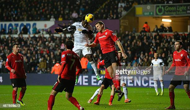 Swansea striker Wilfried Bony beats Ben Turner to score the third goal during the Barclays Premier League match between Swansea City and Cardiff City...