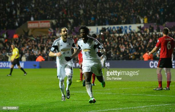 Swansea striker Wilfried Bony celebrates with Chico Flores after scoring the third goal during the Barclays Premier League match between Swansea City...