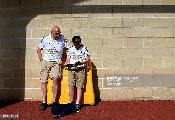 Swansea supporters read a matchday programme prior to the Barclays Premier League match between Swansea City and Everton at the Liberty Stadium on...