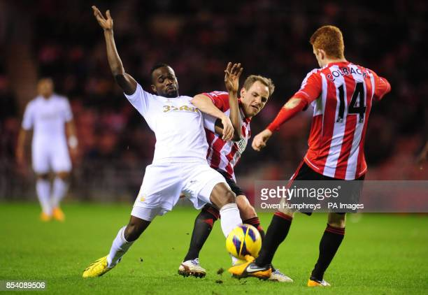 Swansea's Roland Lamah is tackled by Sunderland's David Vaughan and Jack Colbeck during the Barclays Premier League match at the Stadium of Light...