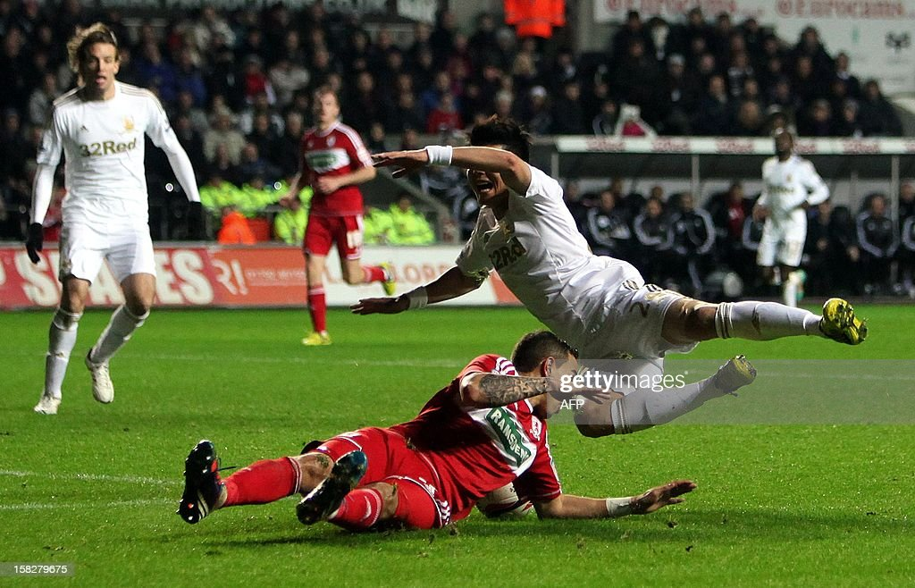 "Swansea's South Korean player Ki Sung-Yeung (R) is tackled by Seb Hines (on ground) of Middlesbrough during the League Cup quarter final match played between Swansea City FC and Middlesbrough FC at Swansea`s Liberty Stadium, Swansea, South Wales on December 12, 2012. Swansea won 1-0. AFP PHOTO/Geoff Caddick "" RESTRICTED TO EDITORIAL USE. No use with unauthorized audio, video, data, fixture lists, club/league logos or ""live"" services. Online in-match use limited to 45 images, no video emulation. No use in betting, games or single club/league/player publications. """