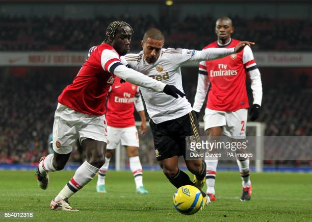 Swansea's Wayne Routledge holds off Arsenal's Bacary Sagna during the FA Cup Third Round Replay at the Emirates Stadium London