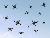Swarm of security drones with surveillance camera flying in the sky. 3D rendering image