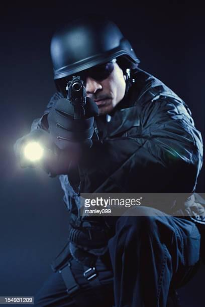 Swat member kneeling with gun and flashlight