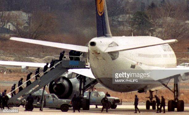 Swat Team members swarm up the stairs into Lufthansa flight 592 after a lone hijacker surrendered 11 February 1993 The plane was hijacked enroute to...