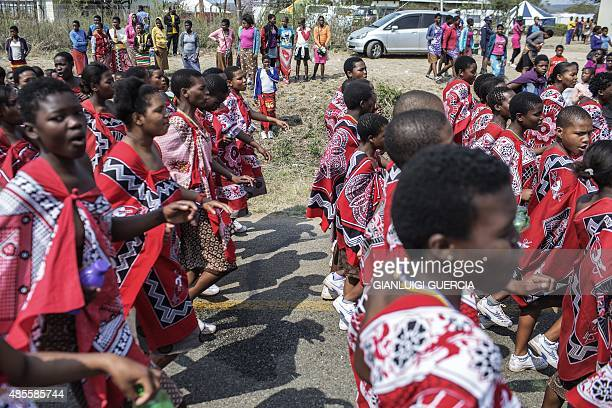 Swazi girls dance and sing as they walk to the Royal palace two day ahead of the traditional reed dance on August 28 2015 on a farm in the outskirts...