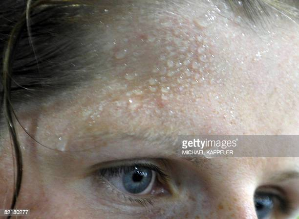 Sweat is seen on the forehead of German rowing athlete Christine Huth at the Gym at the Athlete's Olympic Village in Beijing on August 5 three days...