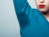 lifestyle shot of woman with her arm raised having sweat mark on her blouse. photo taken in studio.