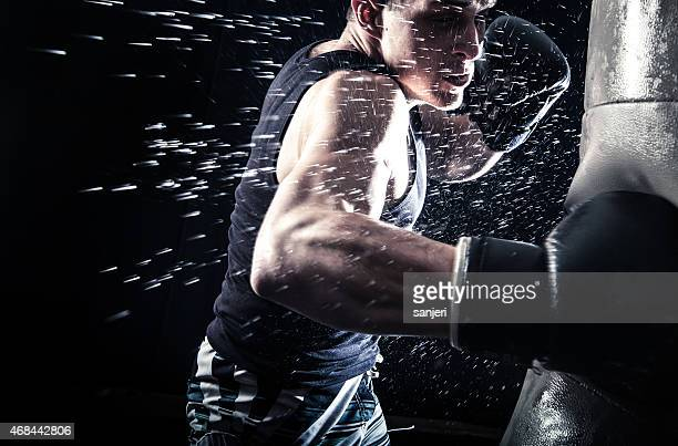 Sweating boxer punching a black bag on black background