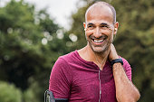 Mature man listening to music while resting after jogging. Happy bald senior man feeling refreshed after exercise. Portrait of a multiethnic man looking away in park while listening to music after fit