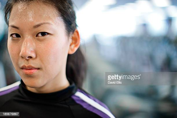 A sweaty woman looks into the camera after she finished her workout