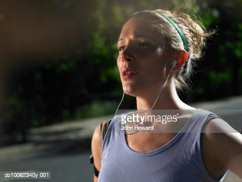 Sweaty young woman wearing mp3 in street, head and shoulders : Stock Photo
