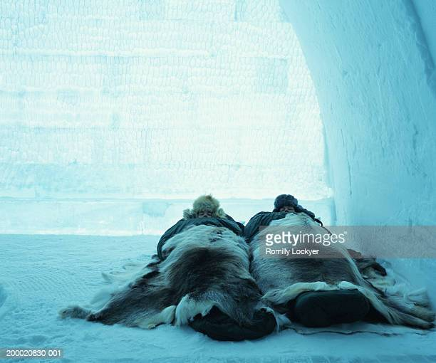 Sweden, Arctic Circle, couple sleeping in igloo