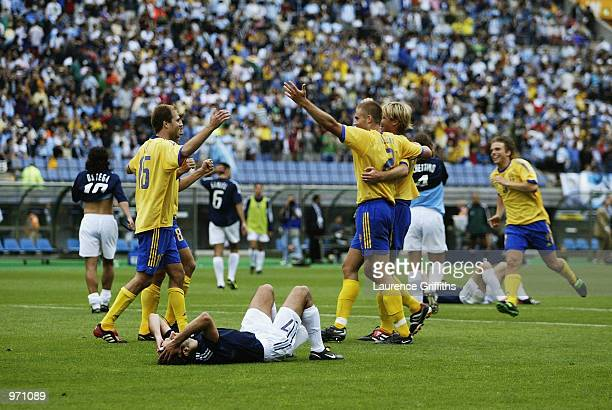 Sweden celebrate as Argentina players lie distraught after the Argentina v Sweden Group F World Cup Group Stage match played at the Miyagi Stadium...