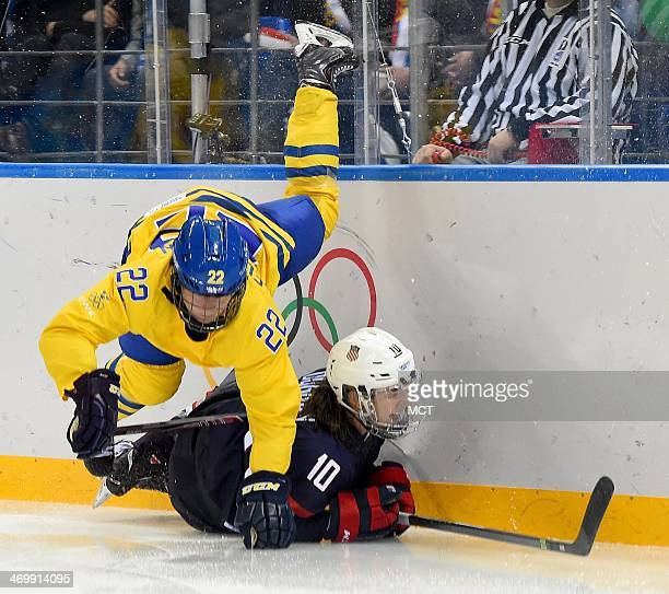 Sweden defenseman Emma Eliasson and USA forward Meghan Duggan go to the ice during the third period in a women's hockey game at the Winter Olympics...