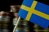 Sweden flag waving with stack of money coins macro