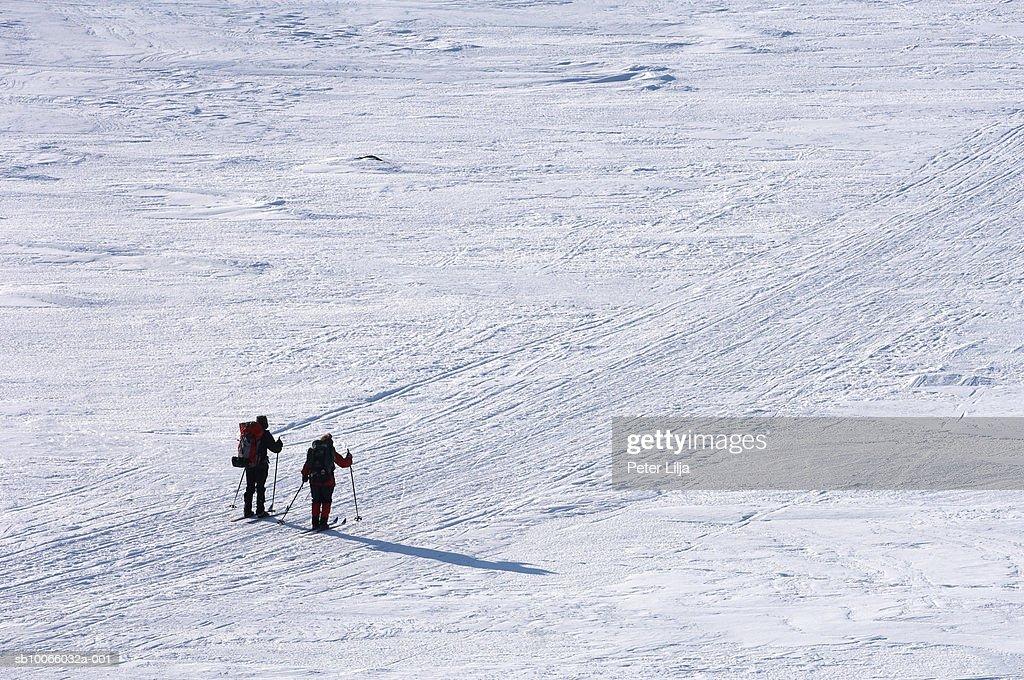 Sweden, Lapland, Kebnekaise, two skiers walking along empty snow field
