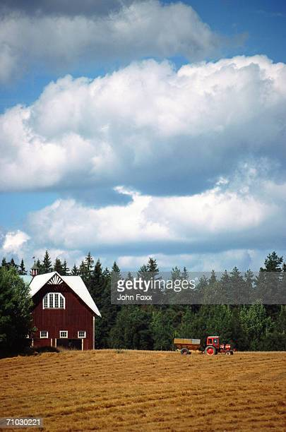 Sweden, Stockholm, Farmhouse with tractor in field