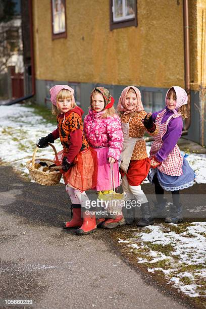 Sweden, Stockholm, four girls in Easter costumes, outdoors