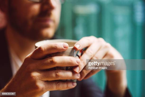 Sweden, Stockholm, Gamla Stan, Man holding coffee cup in cafe, close up of hands