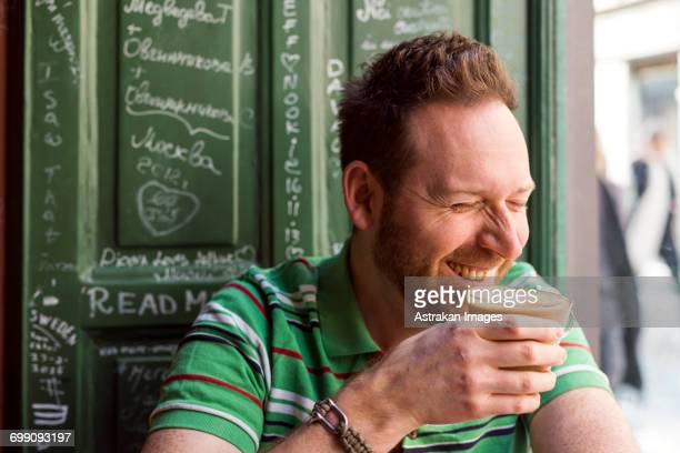 Sweden, Stockholm, Gamla Stan, Man holding coffee cup in cafe, laughing